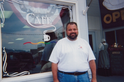 "Michael Corbin outside his restaurant ""Cafe de la Place."" Photo by Peter Dembski."